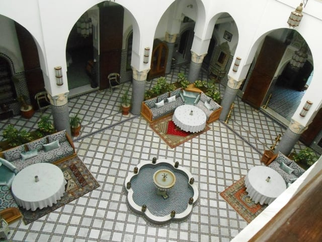 Morocco 's Traditional Riyad With a Water Fountain and Relaxing Space