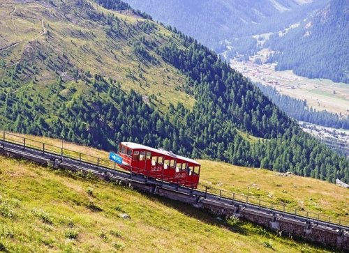 A funicular railway climbing up a steep incline in the Swiss Alps.