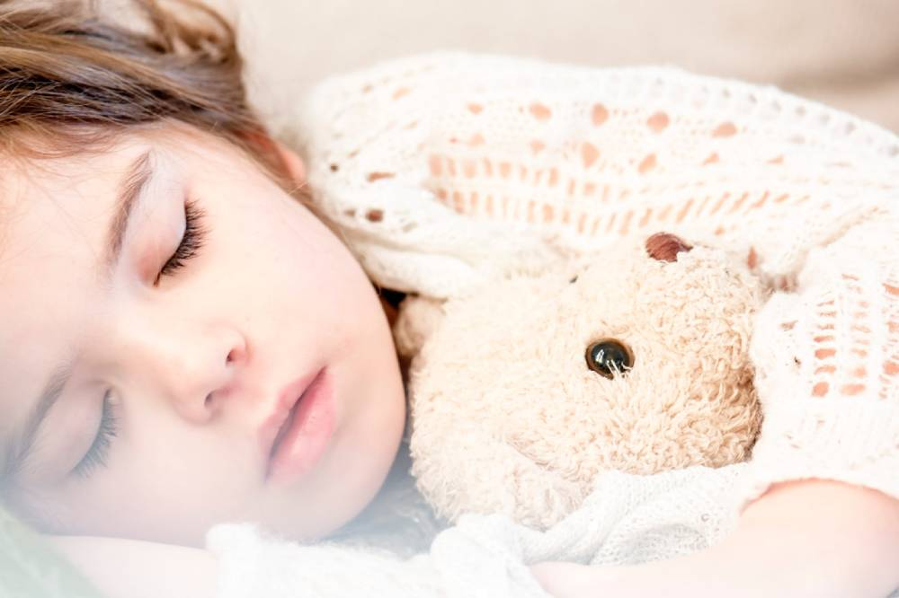 Kid sleeping with teddy - Ways to Get Kids to Sleep on the Plane
